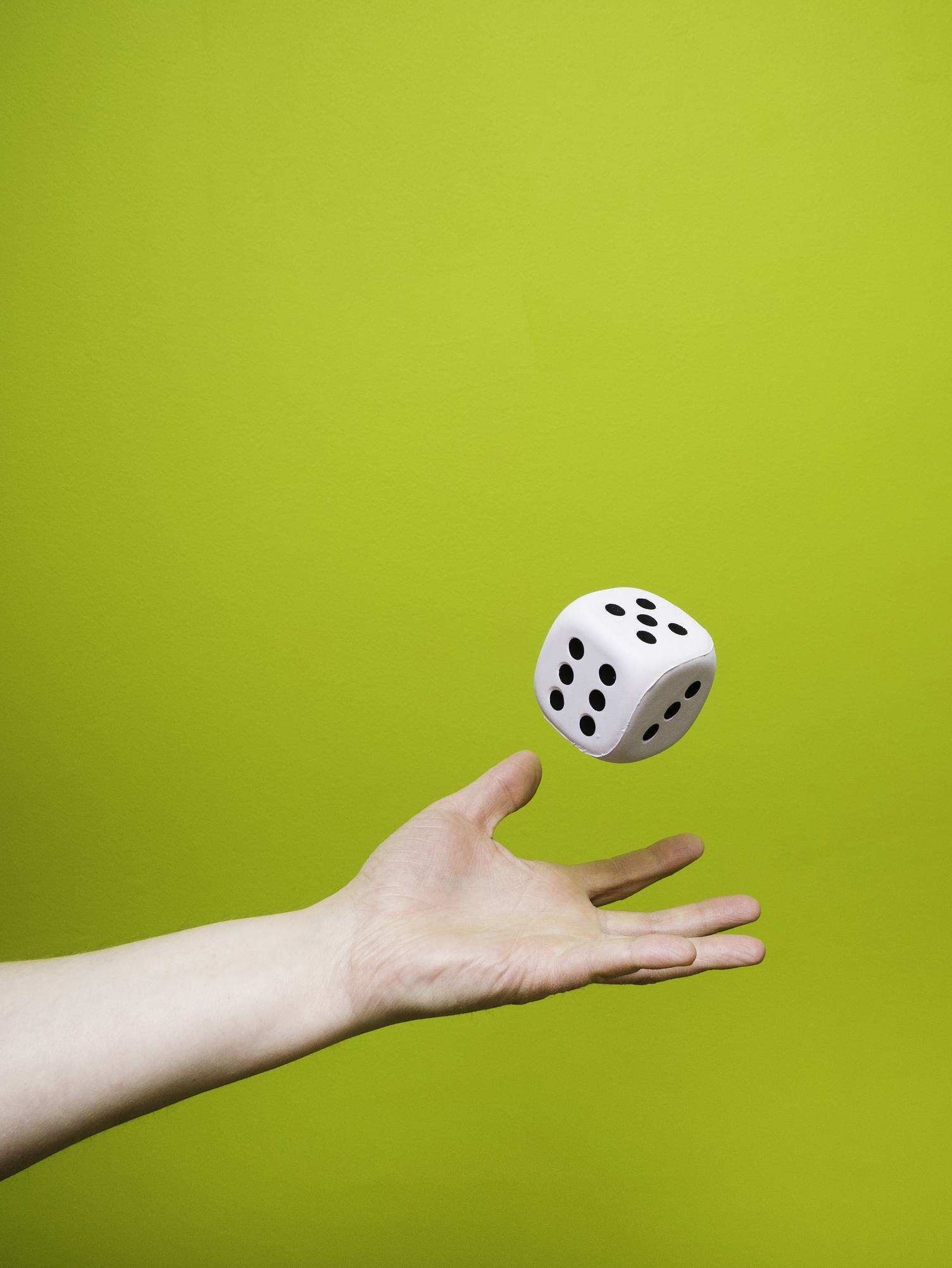 Man Throwing a Large White Dice