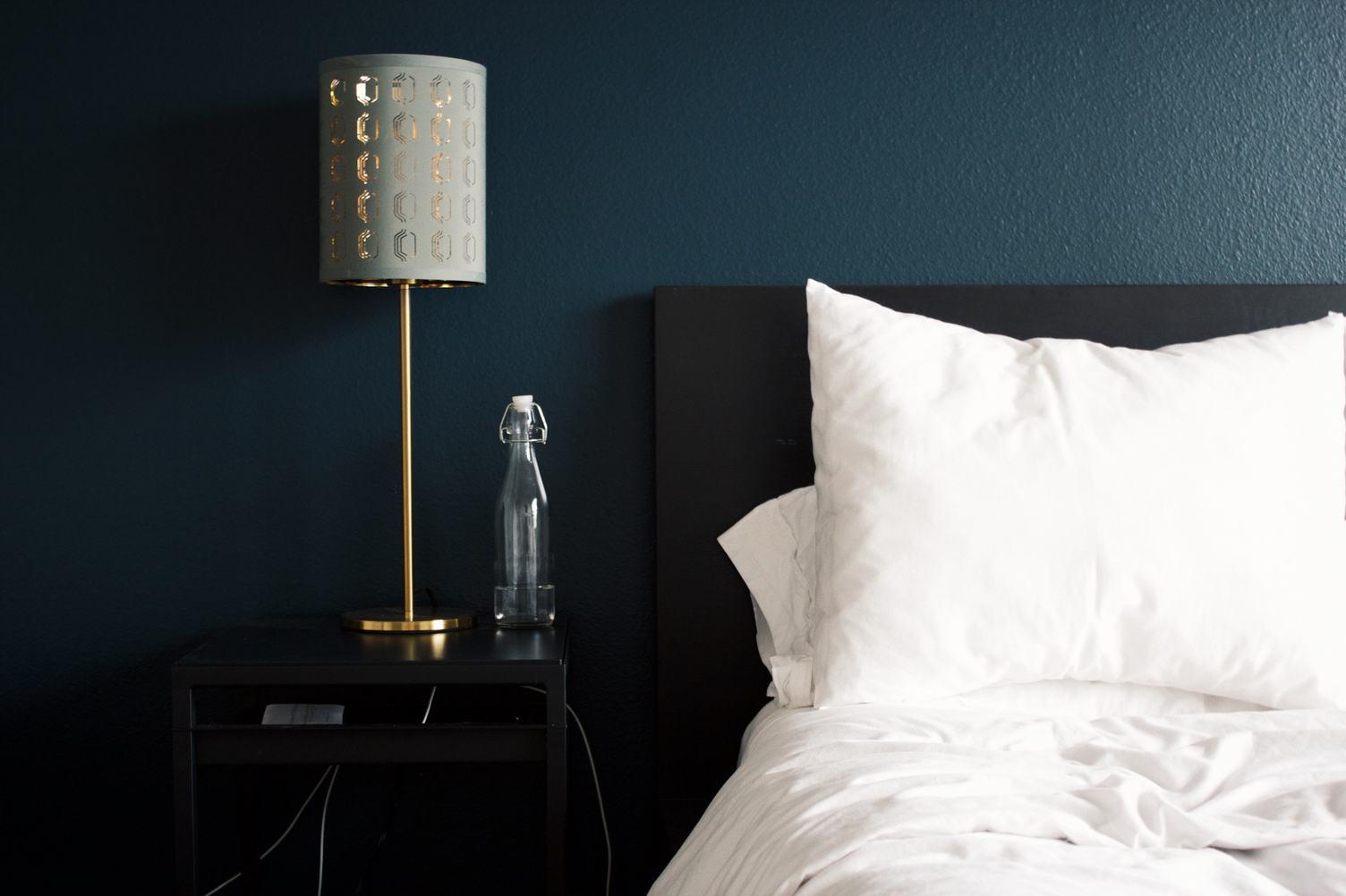 Crumpled White Bed Clothes in Dark Elegant Bedroom
