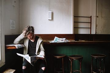 Young Bearded Man Reading a Newspaper in a Cafe