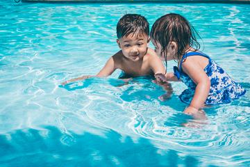 Little Girl and Boy Play in the Swimming Pool