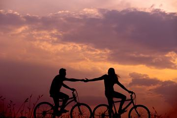 Couple Stretching Arms to each other While Riding Bicycles