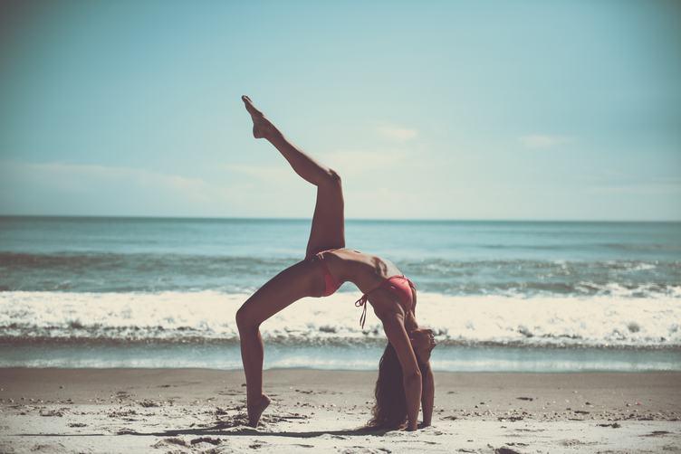 Attractive Woman in Bikini Doing Yoga at the Sea