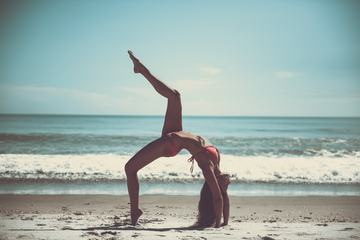 Attractive Woman in Bikini Doing Yoga at the Sea