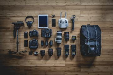 Diverse Personal Photographer Equipment Laying on the Wooden Floor