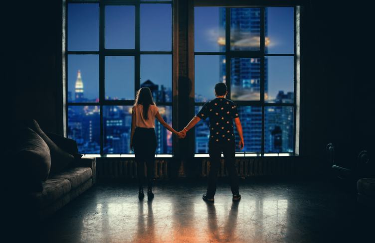 Couple Looking Out of Window in Luxary Apartment