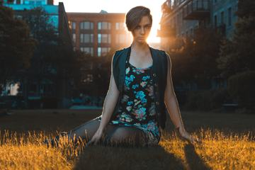 Young Pretty Woman Sitting on the Grass at Sunset