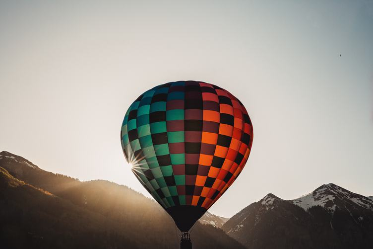 Colorful Hot Air Balloon Flying over Mountains