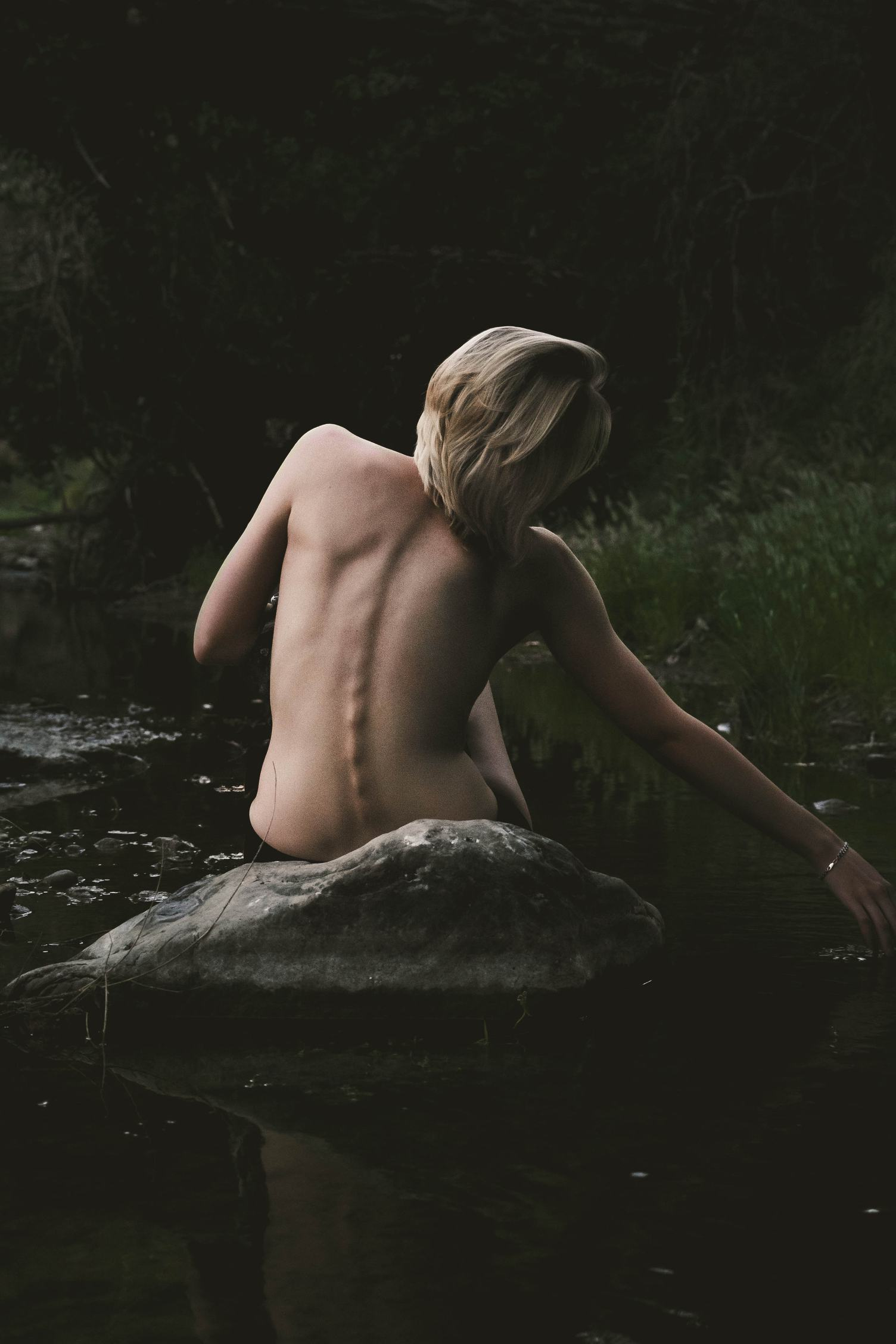 Back View of Nude Woman Sitting on the Rock