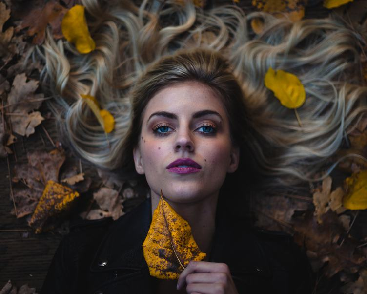Beautifu Woman with Pink Lips Lying on Autumn Leaves