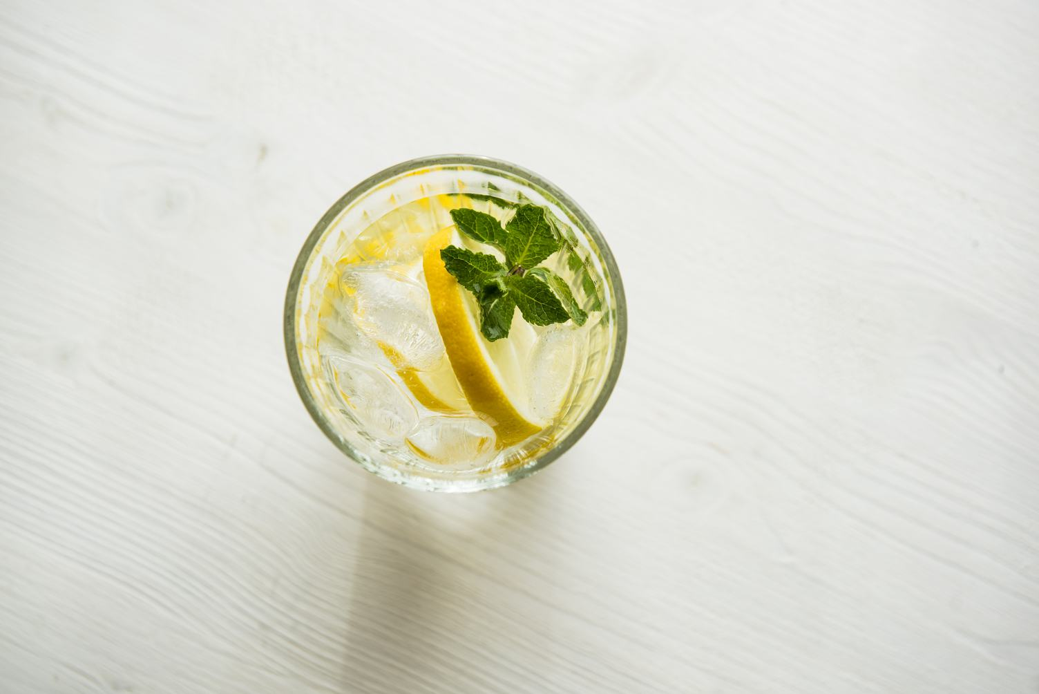 Water with Fresh Lemon, Mint and Ice on Wooden Background