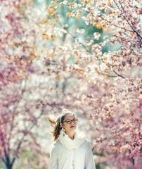 Girl Walking Among Flowering Cherries