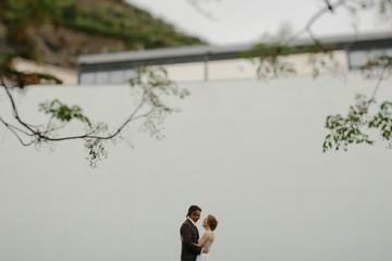 Bride and Groom Standing at a High White Wall