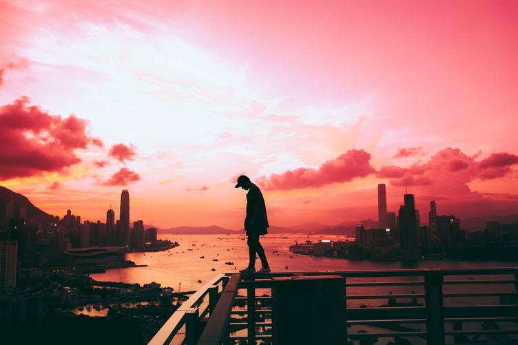 Man walking on the Railing, Victoria Harbor at Sunset, Hong Kong