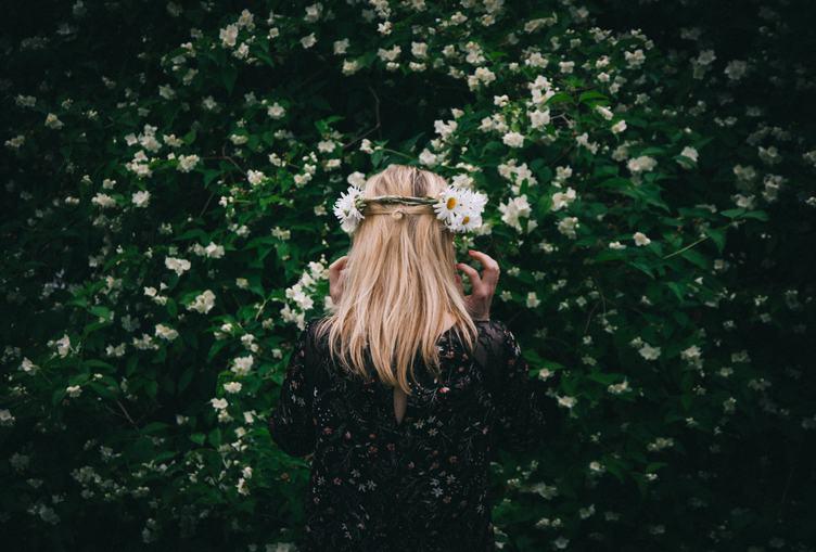 Woman Standing Back by Blooming Jasmine Bush