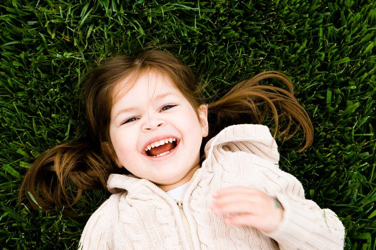 Portrait of a Laughing Little Girl Lying on Green Grass
