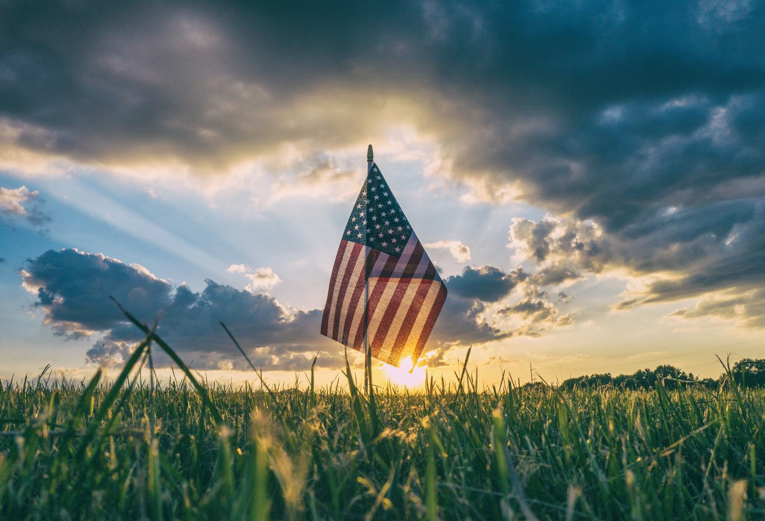 American Flag on the Field against Sunset