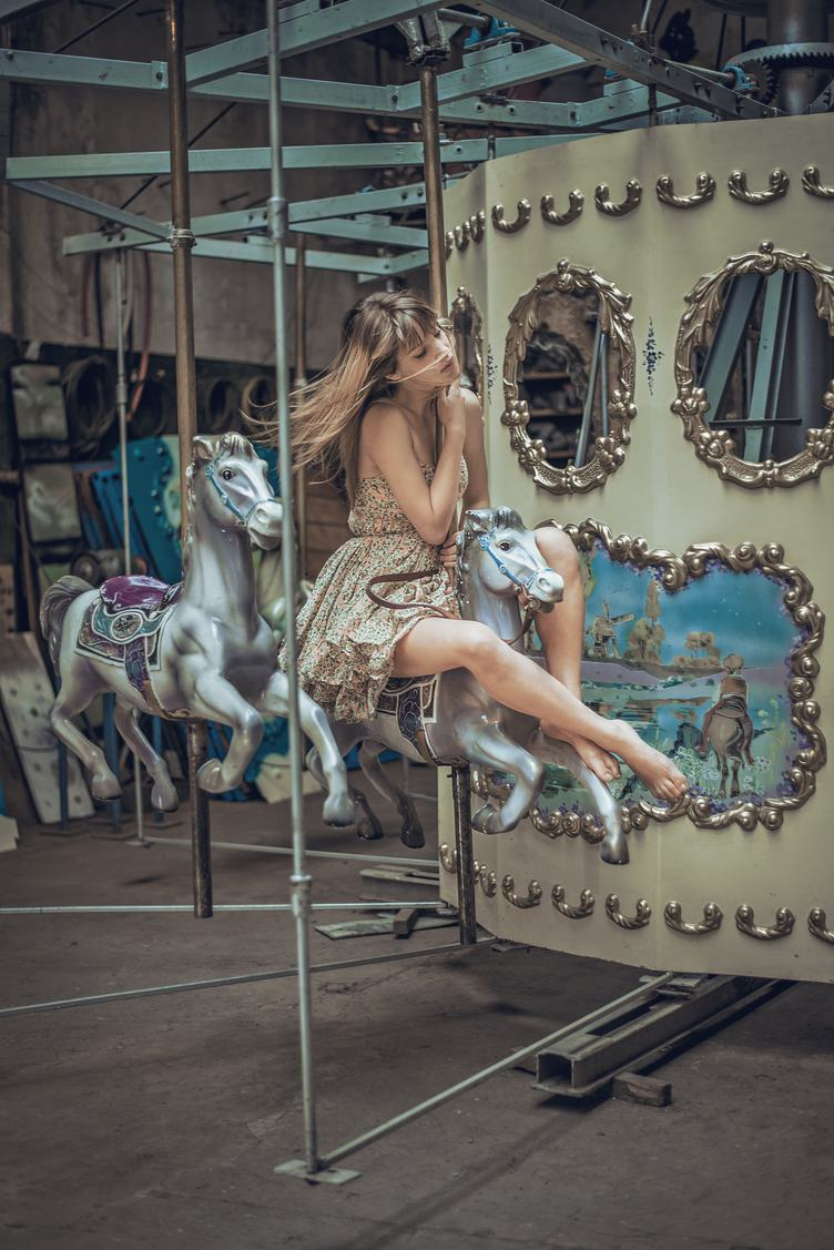 Young Woman Posing on Carousel in Pretty Summer Dress