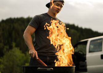 Young Man Burns the Grill Outdoors