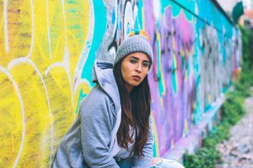 Young Woman Wearing Tracksuit and Glasses Sitting against Graffiti Wall