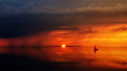 Sailboat Sunset against a Vivid Colorful Sunset with Clouds