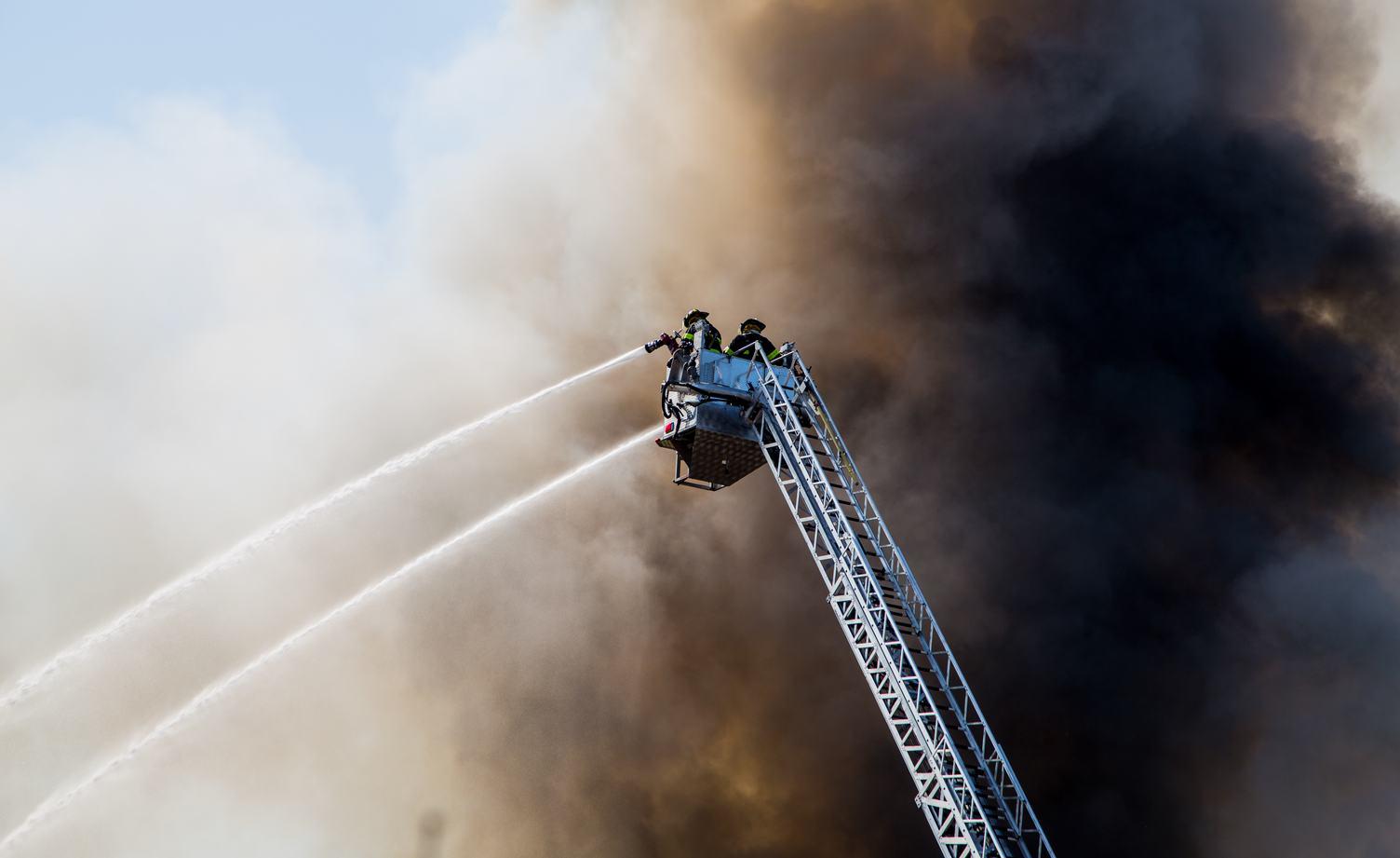 Two Firefmen on the Ladder Spray Water against Black Smoke