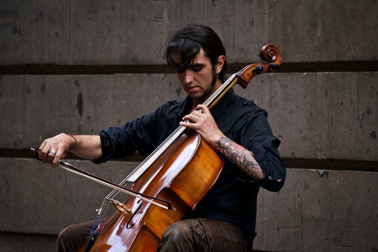 Man with Tattoo Playing Cello Outdoors
