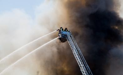 Two Firefmen on the Ladder Spray Water against Black Smoke