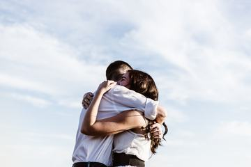Couple Hugging against Sky