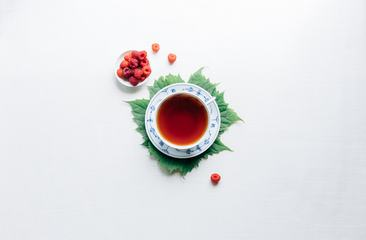 Tea in Porcelain Cup with Raspberries, Flair Lay