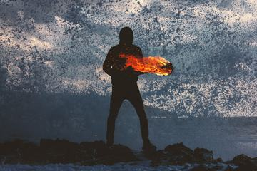 Mysterious Person Holding Fire Torch against Splashing Waves