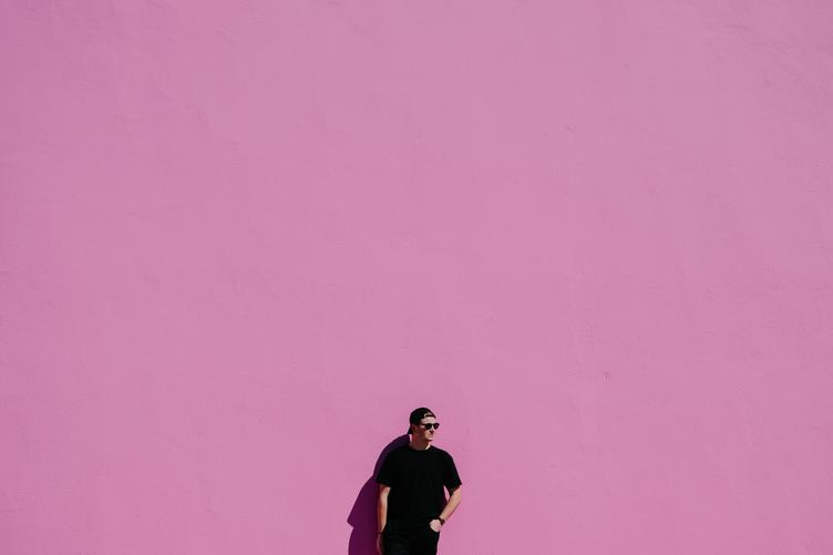 Man in Black T-shirt, Cap andSunglasses Leaning on Pink Wall
