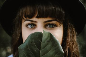 Lovely Brunette Covers Her Mouth behind the Leaf