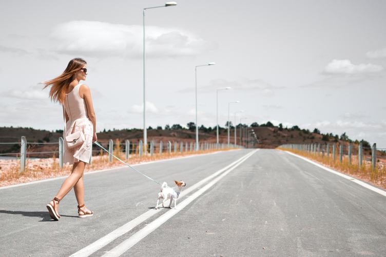 Beautiful Woman Walking with Her Dog on an Empty Road