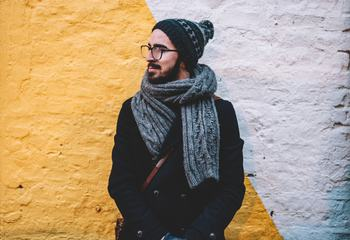 Young Male Wearing Coat, Hat and Scarf against Brick Wall