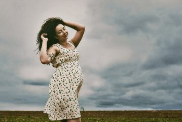 Pregnant Woman with Curly Hair Walking on Field