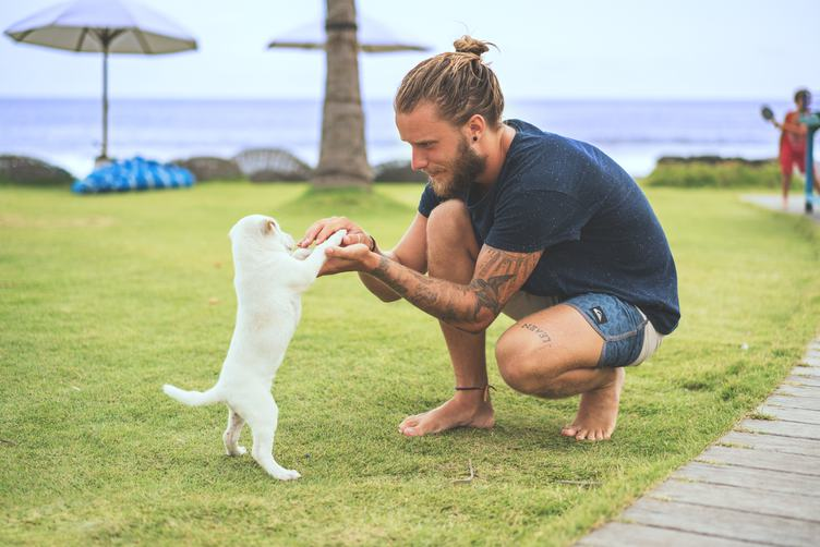 Bearded Guy Holding Little White Puppy Outdoors