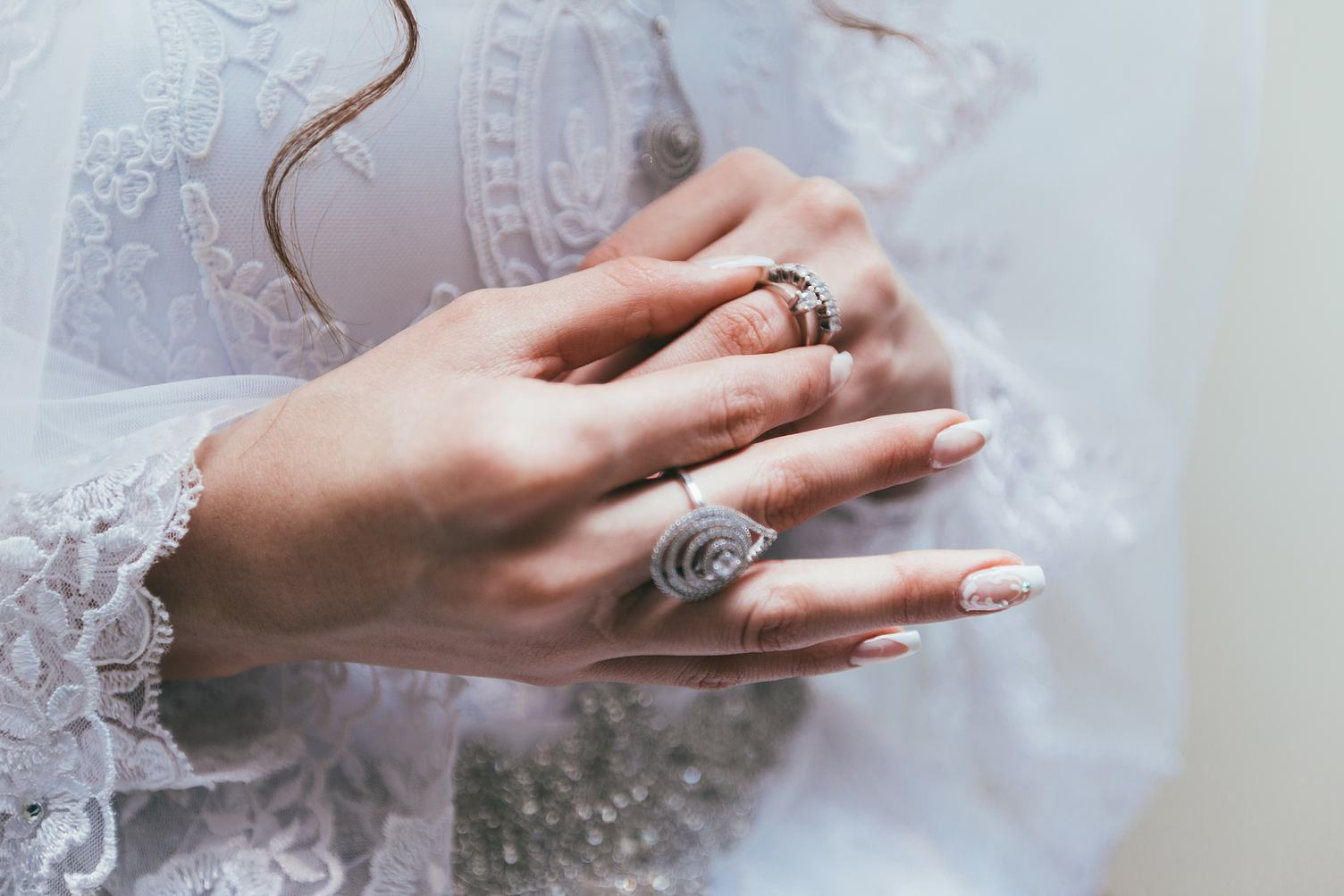 Hands of the Bride against White Wedding Dress