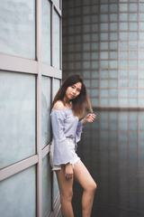 Asian Woman Posing Leaning against the Wall