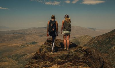 Two Girls Standing Back on Top of a Mountain Enjoying the View