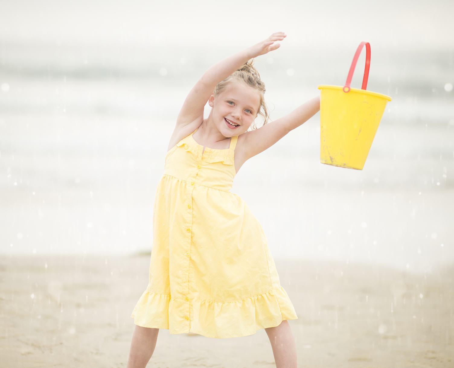 Girl in Yellow Dress Having Fun Playing on a Beach with Bucket