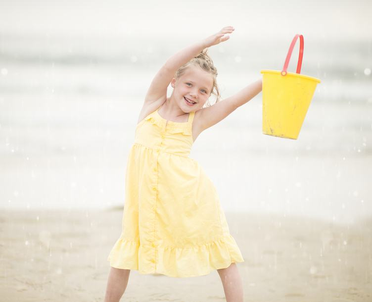 Girl in Yellow Dress Having Fun Playing on a Beach with Bucket