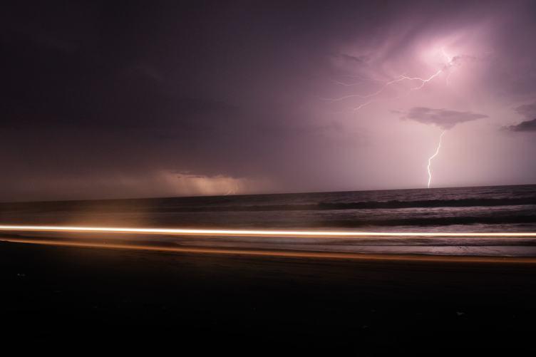 Dark Night with Lightning above Violet Sea