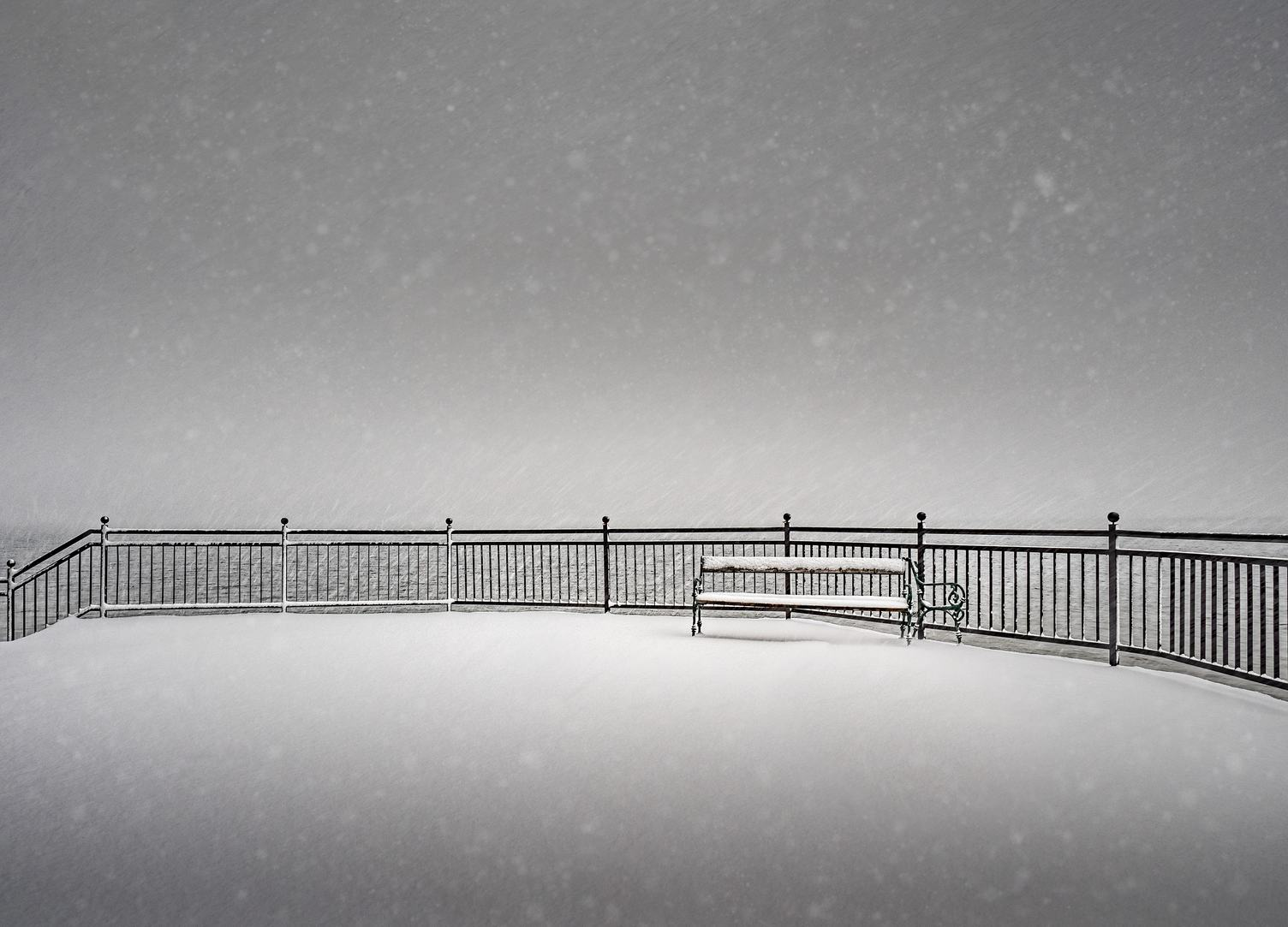 Empty Bench Falling Snow at Winter