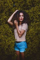 Portrait of Pretty Woman with Long Curly Hair Outdoors