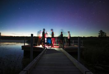 Group of Friends on a Pier by the Lake at Night