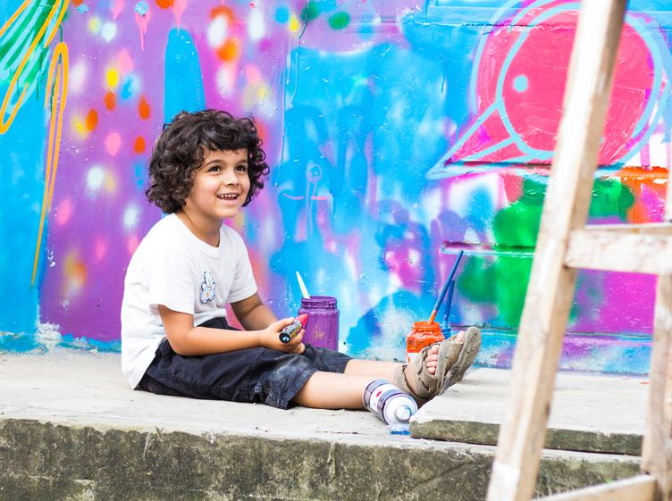 Young Boy Sitting against a Colorful Graffiti Wall