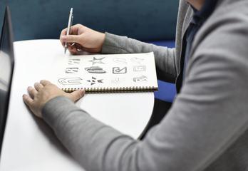 Designer Sketching in His Notebook