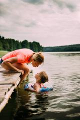 Mother Sitting on a Jetty Her Daughter Swim in the Lake