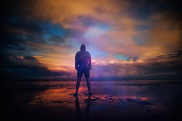 Man Standing behind the Background of a Stunning Sunset