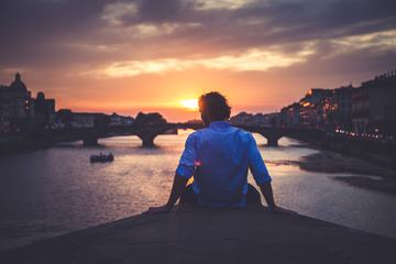 Man Enjoying View of Ponte Santa Trinita in Florence at Sunset